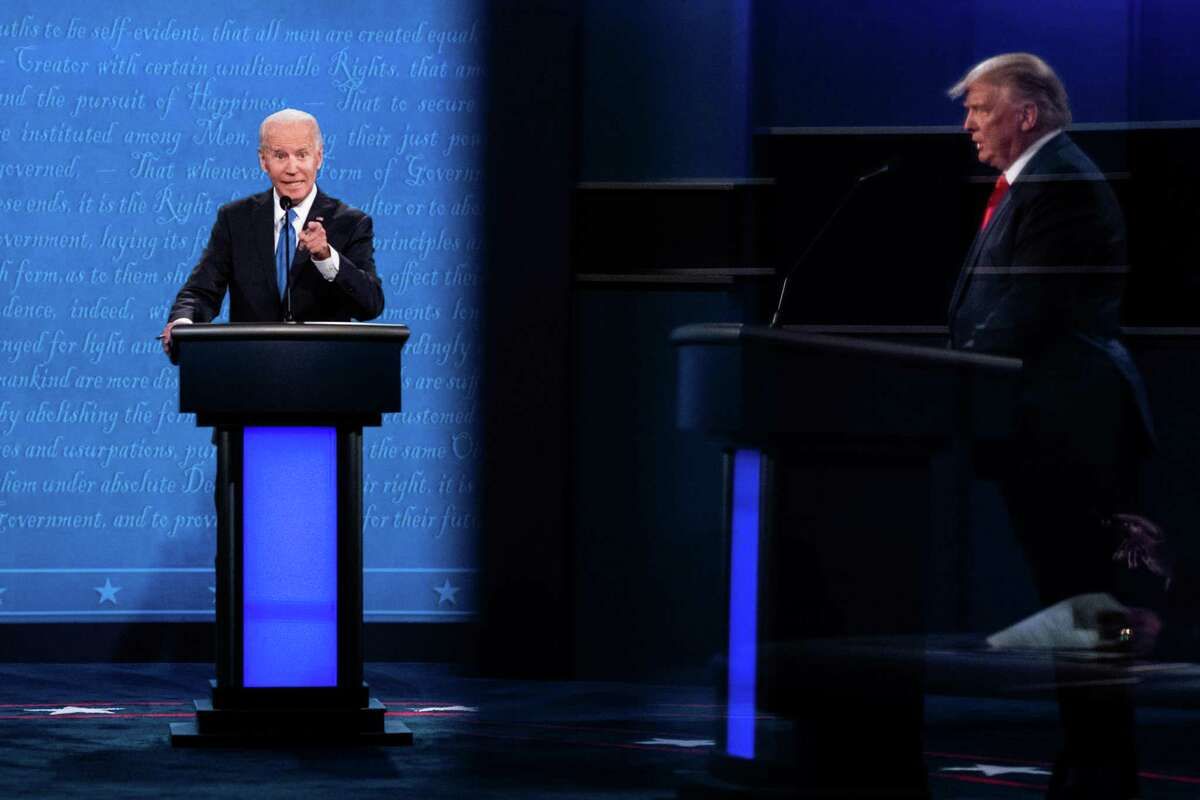 President Donald Trump, seen in reflection, and Joe Biden participate in the final presidential debate, at Belmont University in Nashville, Tenn., Oct. 22, 2020. More than 55 million people watched the candidates' second and final debate, a figure that will rise as data is collected, but will likely fall short of the first debate's 73.1 million. (Erin Schaff/The New York Times)