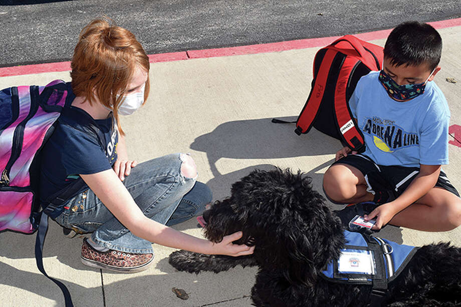 Western fifth-grader Alexis Allen (left) and second-grader Alex Flores pet the district's therapy dog, CoJack, on Thursday during after-school pick-up. Photo: Samantha McDaniel-Ogletree | Journal-Courier