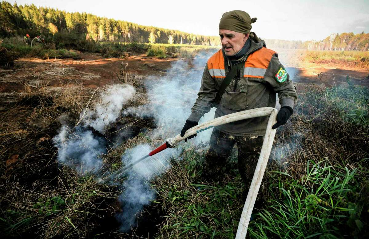 An activist extinguishes a peat fire in a Suzunsky forest next to the village of Shipunovo, south from Siberian city of Novosibirsk on Sept. 11. According to many scientists, Siberia and the Arctic are among the regions most exposed to climate change. They have recorded in recent years records of heat and gigantic fires.