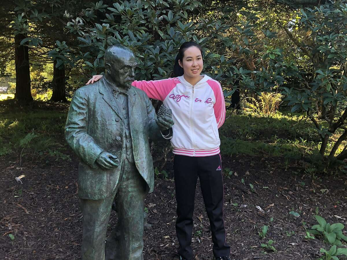Winnie Quock, winner of the Fracchia Prize, stands with the John McLaren statue in the John McLaren Memorial Rhododendron Dell in Golden Gate Park.
