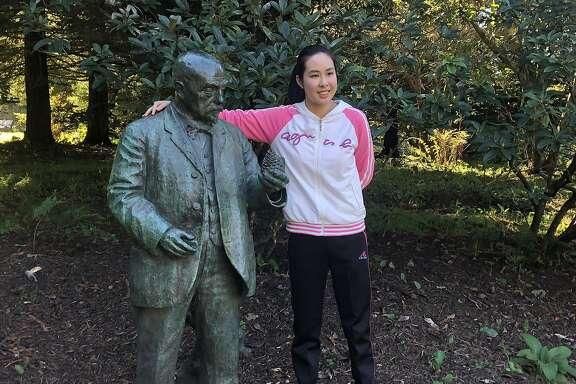 Winnie Quock stands with John McLaren statue in the John McLaren Memorial Rhododendron Dell in Golden Gate Park.
