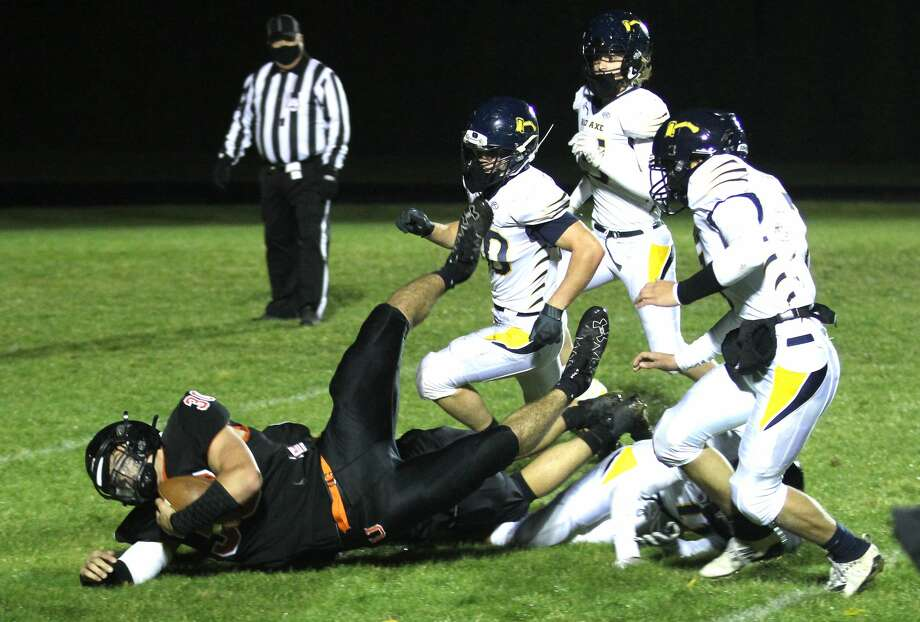 Ubly's Carson Heleski (30) is tackled by Bad Axe defenders after a long gain against the Hatchets on Friday night.