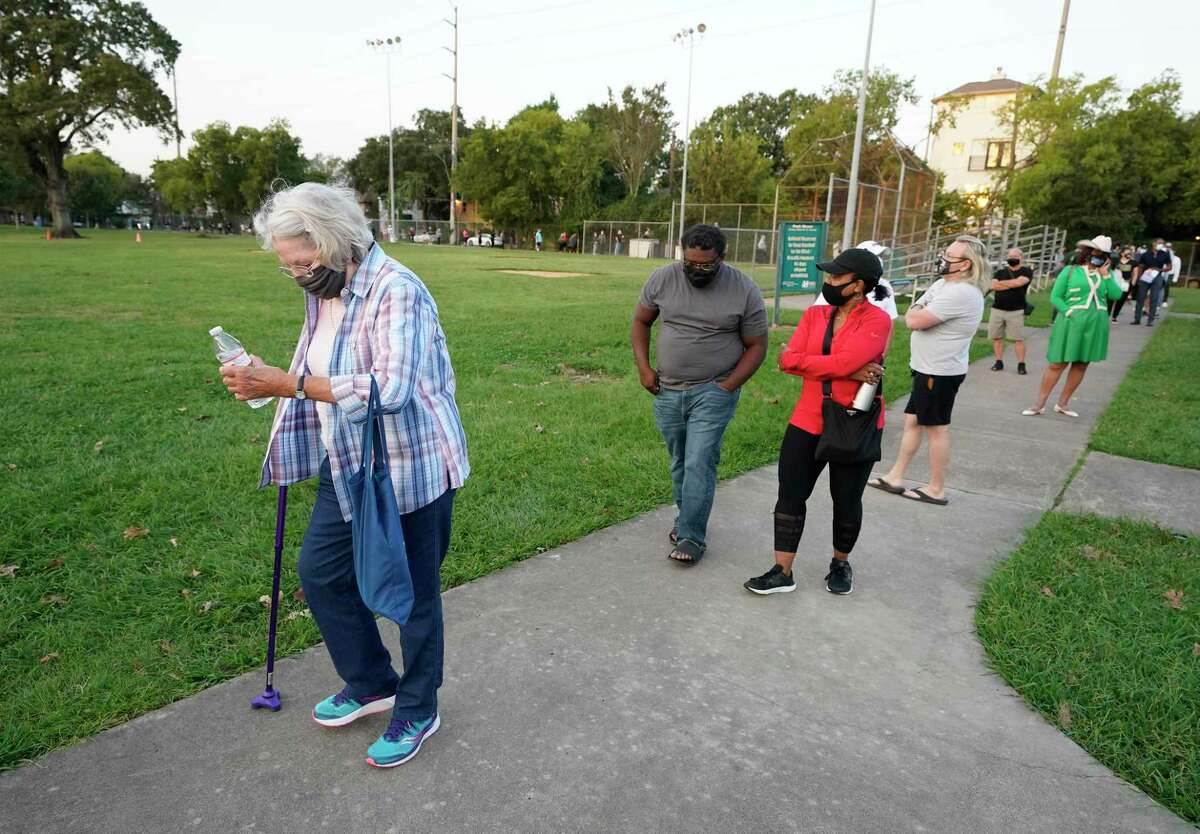 People wait in a long line outside at the Metropolitan Multi-Services Center, 1475 W. Gray St., during the first day of early voting Tuesday, Oct. 13, 2020 in Houston. The line wrapped around the baseball field.