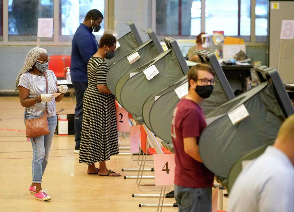 Voters are shown at the Metropolitan Multi-Services Center, 1475 W. Gray St., during the first day of early voting Tuesday, Oct. 13, 2020 in Houston.