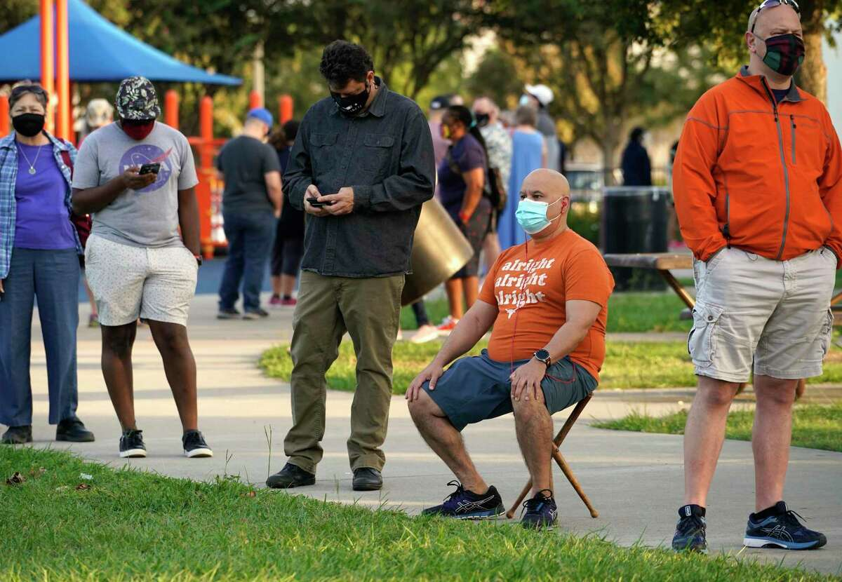 Benny Charles sits as he waits all with others in a long line outside at the Metropolitan Multi-Services Center, 1475 W. Gray St., during the first day of early voting Tuesday, Oct. 13, 2020 in Houston. The line wrapped around the baseball field.