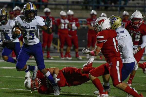 Midland High's Tecumseh Williams (25) carries the ball as Odessa High's Jesse Cervantes attempts to trip him and Midland High's Jakob Vines blocks Odessa High's Mario Valdez on Friday, Oct. 23, 2020 at Ratliff Stadium. Jacy Lewis/Reporter-Telegram