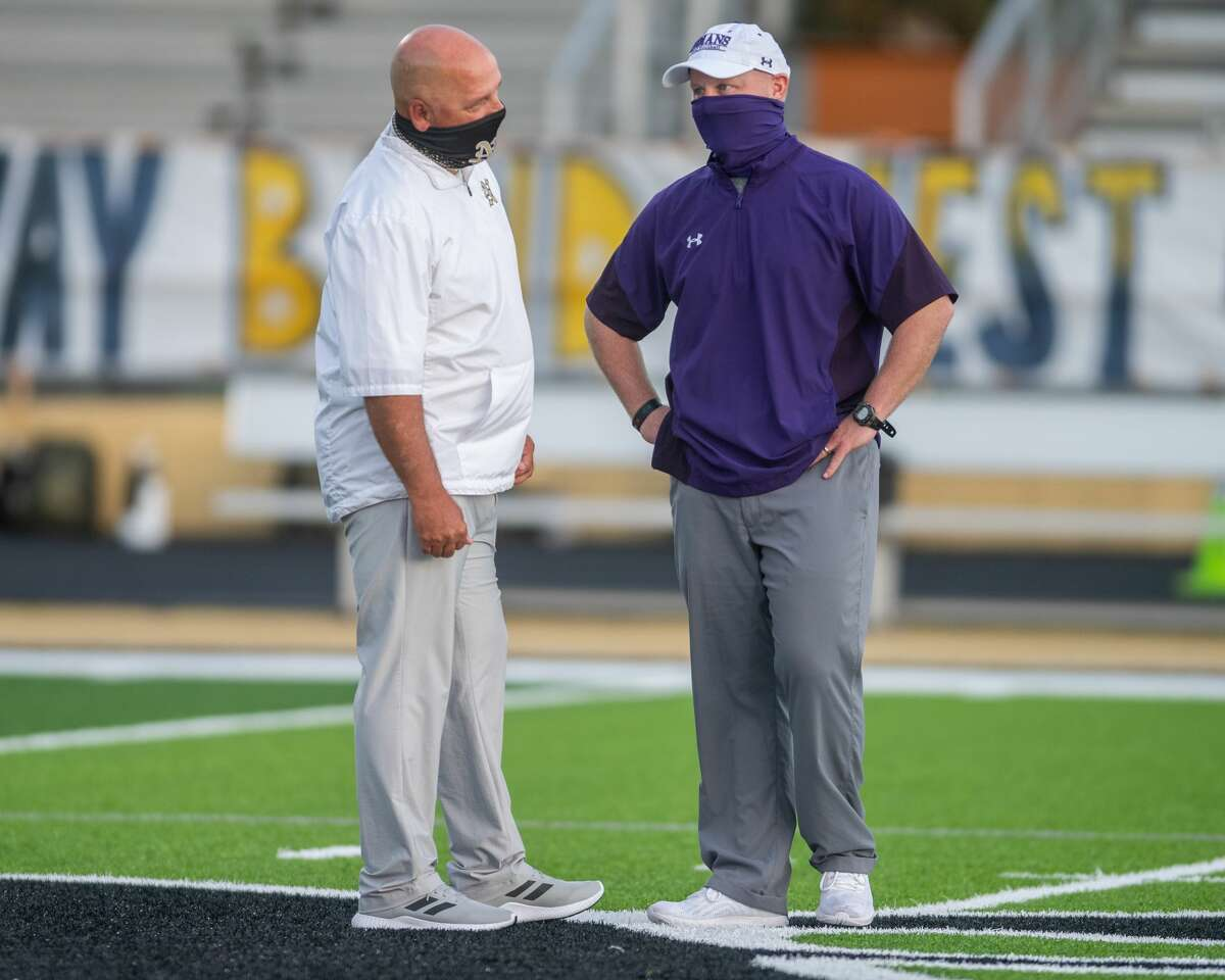 Nederland coach Monte Barrow and PN-G coach Brandon Faircloth meet in the middle of the field before the game. Fans are really into the rivalry between the Port Neches-Groves Indians and the Nederland Bulldogs. Photo made on October 23, 2020. Fran Ruchalski/The Enterprise