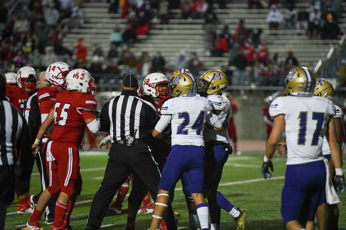Odessa High?•s Emilio Dominguez (59) and Midland High?•s Tecumseh Williams (25) and Jordan Springer are broken up by a referee Friday, Oct. 23, 2020 at Ratliff Stadium. Jacy Lewis/Reporter-Telegram