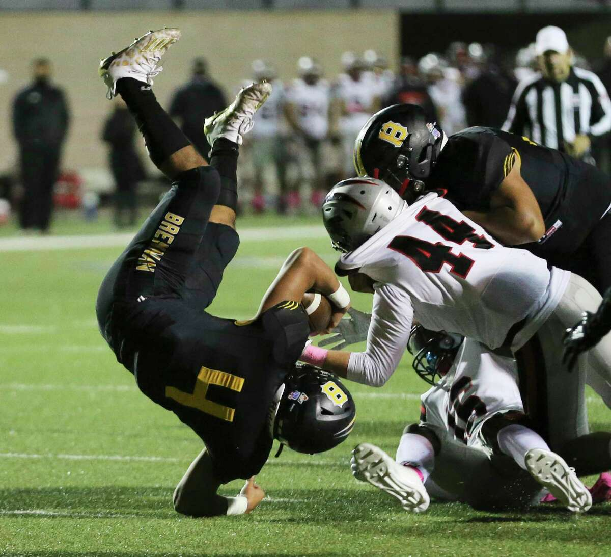 Brennan's Justino Escobar (04) flips over as Stevens' Evan McCall (44) and Leonard Adams (16) makes the stop during their football game at Farris Stadium on Friday, Oct. 23, 2020.