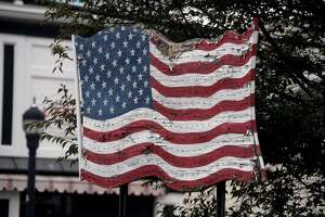 This weathered American flag banner hangs continually at the head of the Milford Green, in Milford on Wednesday.
