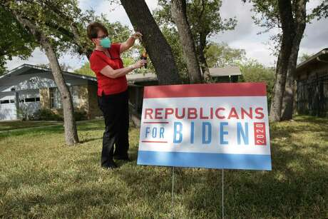 Monica Flynn trims trees in her yard. She's a Republican who will be voting for Democrat Joe Biden and has a sign in her yard to show it.