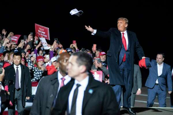 President Donald Trump throws hats to the crowd as he arrives for a campaign event at the Duluth International Airport on Sept. 30, in Duluth, Minn.