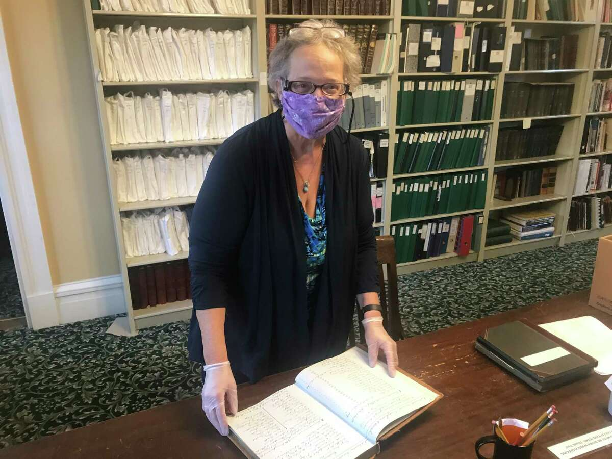 Kathy Sheehan, the historian for the city of Troy and Rensselaer County, with the Oakwood Presbyterian Church records from the 19th century at the Hart Cluett Museum Library, 57 Second St., Troy, N.Y.