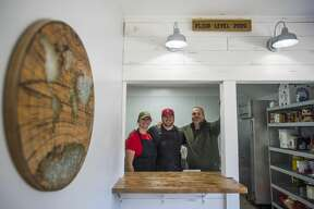 From left, Abbi Brady, Jack Brady and Mike Brady pose for a photo inside the business as it reopens Saturday, Oct. 24, 2020, for the first time since the building was damaged during the May 19 dam failures and flooding. (Katy Kildee/kkildee@mdn.net)