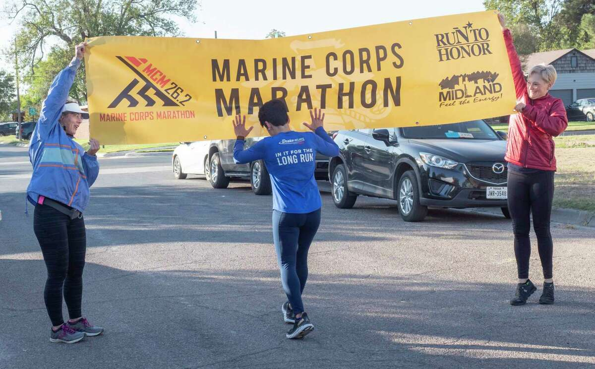 Gaby Garza is the first to run under the finish line, held up by Degen Fricker and Angela Deaver, 10/24/2020 morning during the Marine Corps Marathon, being run in Midland after the national marathon was canceled. Runners from Midland have run the marathon in honor of Patrick Wayland, Midland High grad and Naval Academy graduate who died in a training accident in 2011. Tim Fischer/Reporter-Telegram