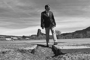 Navajo Nation President Jonathan Nez stands along a crumbling road and sidewalk in Navajo, N.M., in April 2019. Nearly three quarters of the roads are unpaved in Navajo Nation, which stretches into Arizona, New Mexico and Utah.