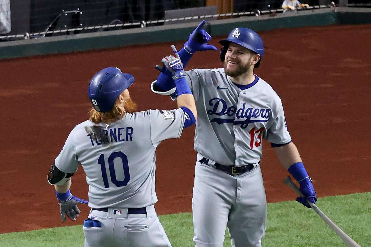 ARLINGTON, TEXAS - OCTOBER 23: Justin Turner #10 of the Los Angeles Dodgers is congratulated by Max Muncy #13 after hitting a solo home run against the Tampa Bay Rays during the first inning in Game Three of the 2020 MLB World Series at Globe Life Field on October 23, 2020 in Arlington, Texas. (Photo by Tom Pennington/Getty Images)