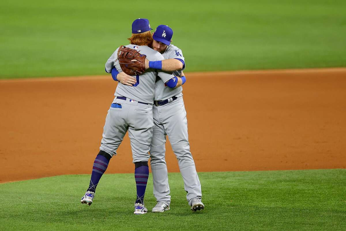 ARLINGTON, TEXAS - OCTOBER 23: Justin Turner #10 and Max Muncy #13 of the Los Angeles Dodgers celebrate the teams 6-2 victory against the Tampa Bay Rays in Game Three of the 2020 MLB World Series at Globe Life Field on October 23, 2020 in Arlington, Texas. (Photo by Ronald Martinez/Getty Images)