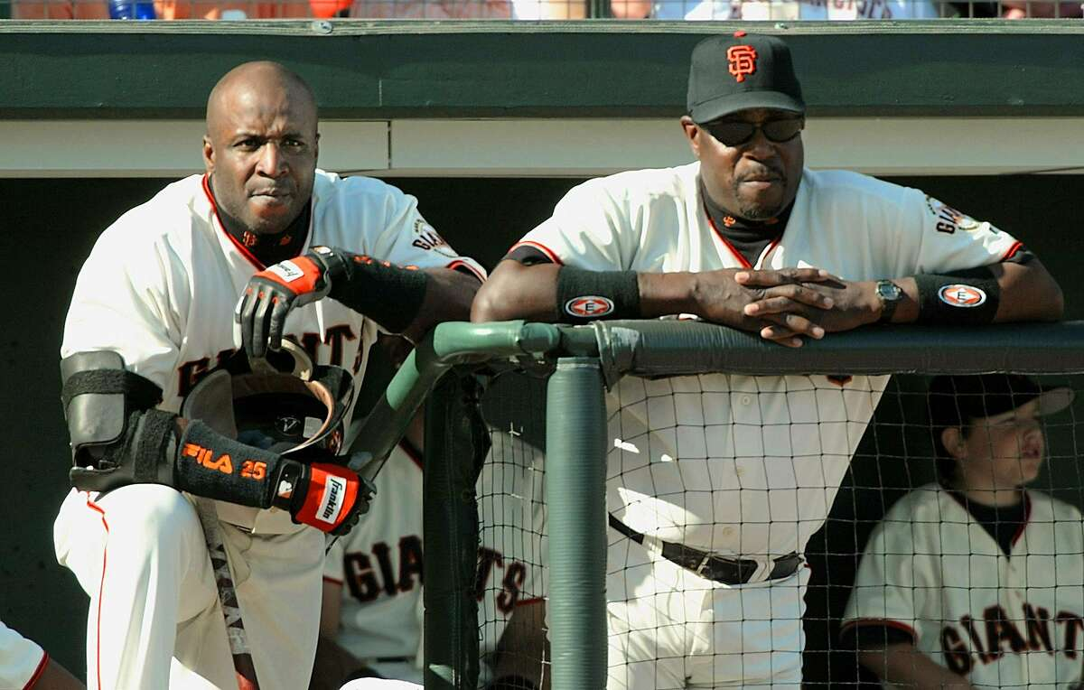 Barry Bonds (L) and manager Dusty Baker (R) of the San Francisco Giants watch from the dugout 12 October 2002, during game 3 of the National League Championship Series against the St. Louis Cardinals at Pacific Bell Park in San Francisco, CA. The Giants lead 2-0 in the best-of-seven series. AFP PHOTO/Jeff HAYNES (Photo credit should read JEFF HAYNES/AFP/Getty Images)
