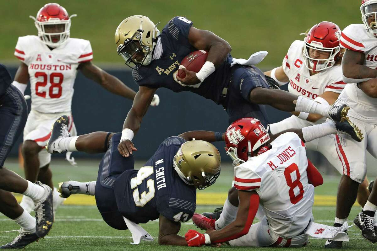 ANNAPOLIS, MARYLAND - OCTOBER 24: Quarterback Dalen Morris #8 of the Navy Midshipmen is tackled by cornerback Marcus Jones #8 of the Houston Cougars during the second quarter at Navy-Marine Corps Memorial Stadium on October 24, 2020 in Annapolis, Maryland. Due to the Covid-19 pandemic, Navy athletics announced they would not allow general admission fans, only midshipmen.