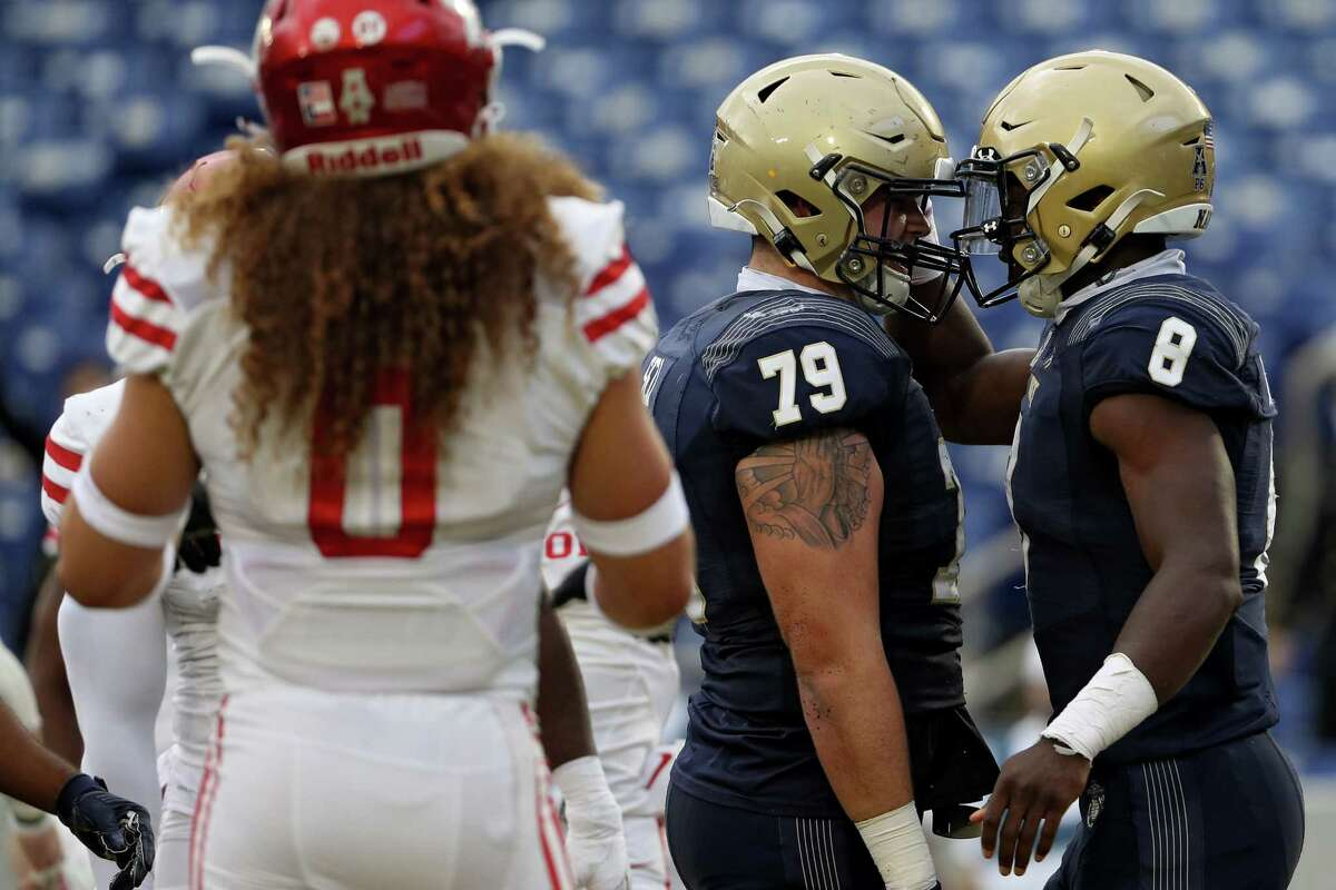 ANNAPOLIS, MARYLAND - OCTOBER 24: Quarterback Dalen Morris #8 of the Navy Midshipmen celebrates his touchdown with teammate center Justin Self #79 against the Houston Cougars during the first quarter at Navy-Marine Corps Memorial Stadium on October 24, 2020 in Annapolis, Maryland. Due to the Covid-19 pandemic, Navy athletics announced they would not allow general admission fans, only midshipmen.