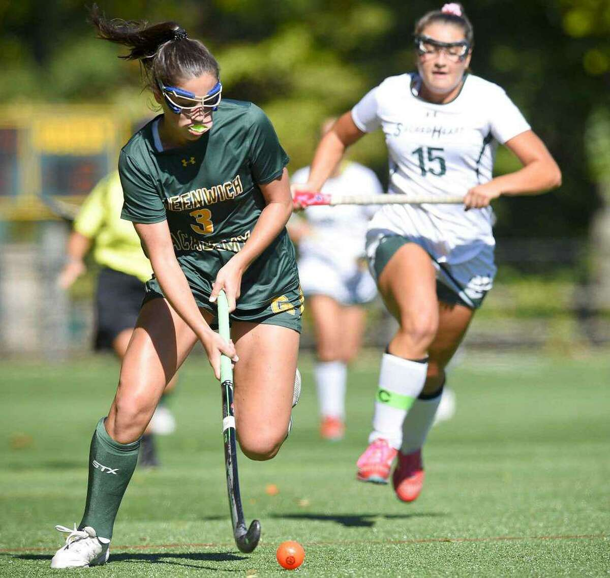 Lily Murray, left moves the ball up the field for the Greenwich Academy field hockey team in its game against Sacred Heart Greenwich in 2010. Murray is one of the senior captains of the Greenwich Academy field hockey team this season.