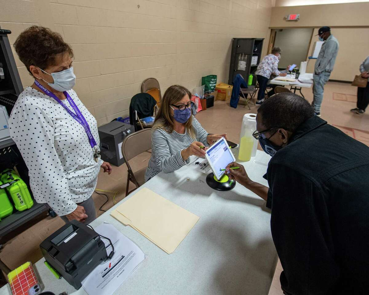 Margaret Rutledge and Dorothy Earnest take information from voter Rodney Smith at the Pine Grove United Methodist Church on Central Avenue in Colonie, NY, during the first day of early voting in New York state on Saturday, Oct. 24, 2020 (Jim Franco/special to the Times Union.)