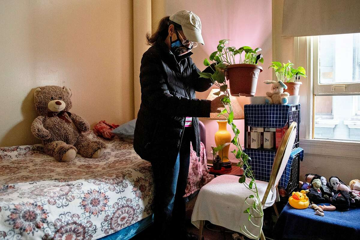 Eva Maggard, 70, untangles her pothos plant after arriving at her home in the Tenderloin neighborhood of San Francisco, Calif. Thursday, October 22, 2020. Maggard lives alone in a Tenderloin hotel and has been seriously isolated during the pandemic, sometimes spending days at a time in her room. She has recently started venturing outside for short walks and occasional trips to the store, and is attending a technology class at the Curry Senior Center that just resumed in-person meetings last month.