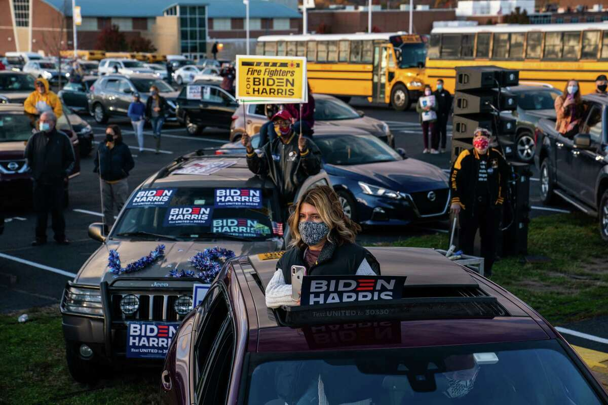 Supporters listen to former vice president Joe Biden during a drive-in event at Dallas High School in Dallas, Pa.