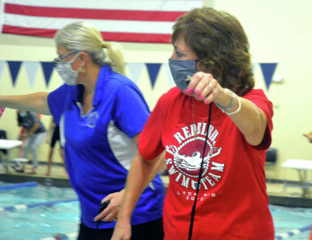Alton High swim coach Nancy Miller, right, and Marquette coach Jennifer Roth gives instructions during Saturday's IHSA sectional at Edwardsville.