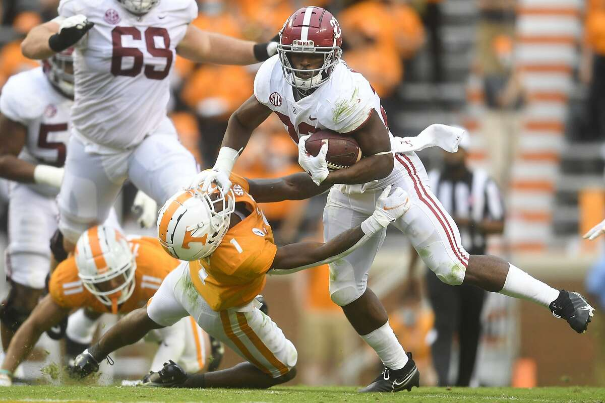 Alabama running back Najee Harris (22) pushes back Tennessee defensive back Trevon Flowers (1) in the second half during an NCAA college football game in Knoxville, Tenn., Saturday, Oct. 24, 2020. (Caitie McMekin/Knoxville News Sentinel via AP)