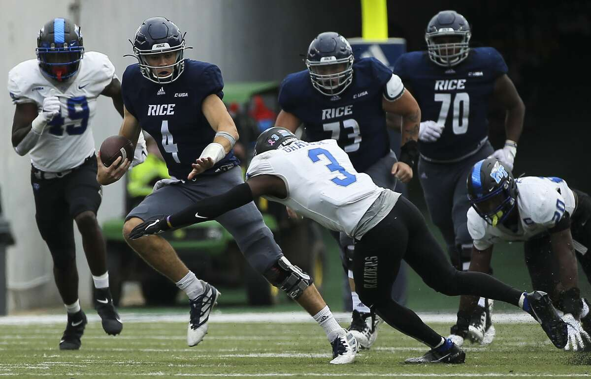 Rice Owls quarterback Mike Collins (4) runs the ball while Middle Tennessee Blue Raiders safety Gregory Grate Jr. (3) is trying to tackle him during the third quarter of a CUSA conference game Saturday, Oct. 24, 2020, at Rice Stadium in Houston. Middle Tennessee Blue Raiders defeated Rice Owls 40-34 in double overtime.