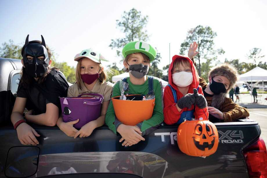 A group of children sit in the back of a truck at Sawdust Park and Ride. Photo: Gustavo Huerta, Houston Chronicle / Staff Photographer / 2020 © Houston Chronicle
