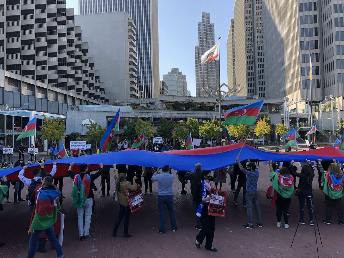 People of Azerbaijani heritage unfurl a giant flag as they gather at Embarcadero Plaza to highlight a conflict in their home region on Saturday.