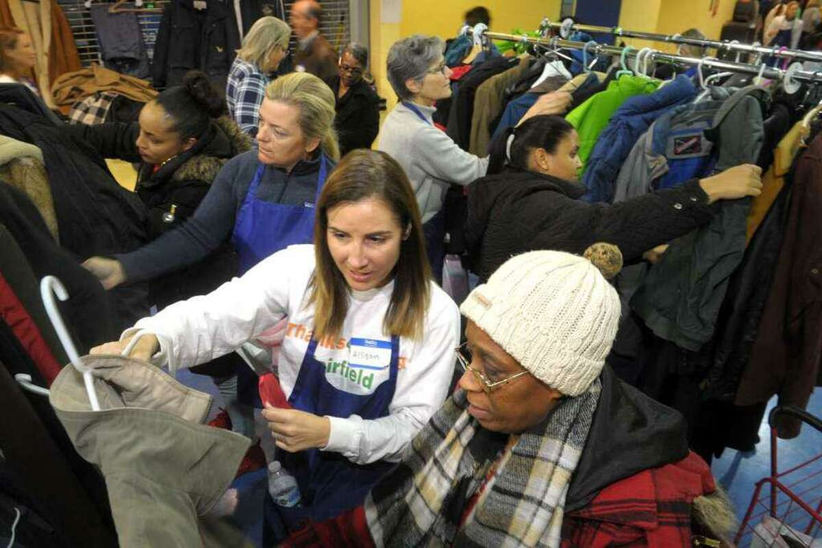 In this file photo, Volunteer Allison Reiling, left, helps Lisa Neal find a winter coat for her son during the Bridgeport Rescue Mission's Great ThanksGiving Project at Webster Bank Arena, in Bridgeport, Conn. in 2019.