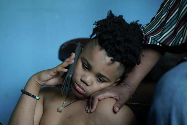 Ahav speaks with his therapist while his mother, Kelli Lewis, provides a supporting touch. Ahav has mental health issues that have worsened during the pandemic.