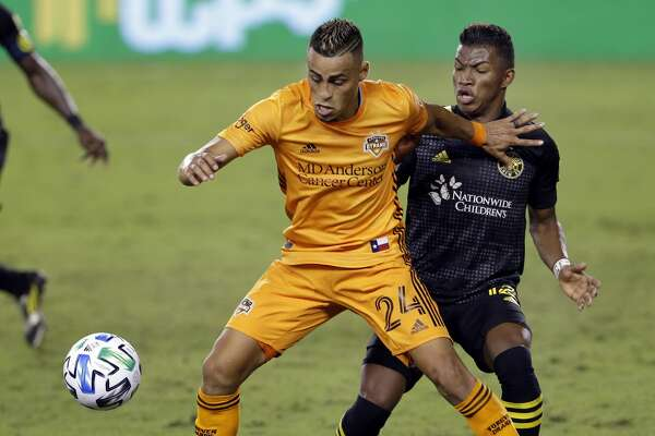 Houston Dynamo midfielder Darwin Ceren (24) holds back Columbus Crew midfielder Luis Diaz, right, during the second half of an MLS soccer match Saturday, Oct. 24, 2020, in Houston. (AP Photo/Michael Wyke)
