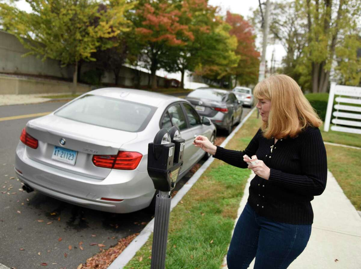 Marianne Hillmer feeds the meter for her car parked on Benedict Place in Greenwich, Conn. Wednesday, Oct. 21, 2020. Hillmer's street does not offer residential parking permits and as a senior citizen she needs close access to her vehicle. She is forced to find street parking near her building and feed the parking meter in two-hour increments throughout the day.