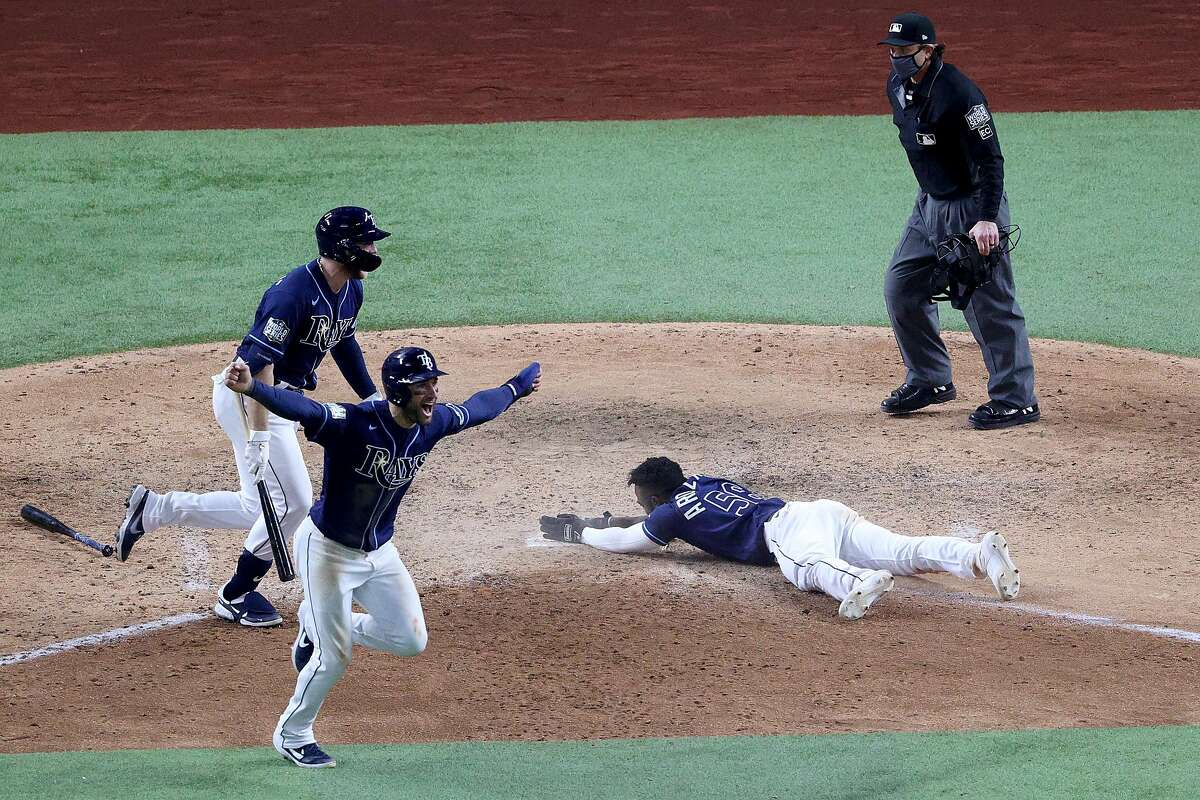 ARLINGTON, TEXAS - OCTOBER 24: Randy Arozarena #56 of the Tampa Bay Rays slides into home plate during the ninth inning to score the game winning run to give his team the 8-7 victory as Kevin Kiermaier celebrates against the Los Angeles Dodgers in Game Four of the 2020 MLB World Series at Globe Life Field on October 24, 2020 in Arlington, Texas. (Photo by Sean M. Haffey/Getty Images)