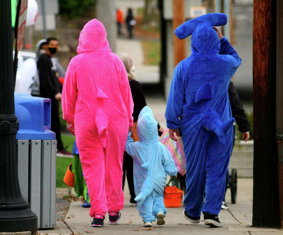 Dressed up as a family of sharks, Ashley and Ralph Dellaventura, of Stratford, walk with their child Avery, 2, as they wander through downtown Milford, Conn., taking part in a safe, socially distant way to enjoy the Halloween holiday on Saturday Oct. 24, 2020. Sponsored by Spinnaker Milford, participating shops put a scarecrow out front and offered treats to local kids. Photo: Christian Abraham / Hearst Connecticut Media / Connecticut Post