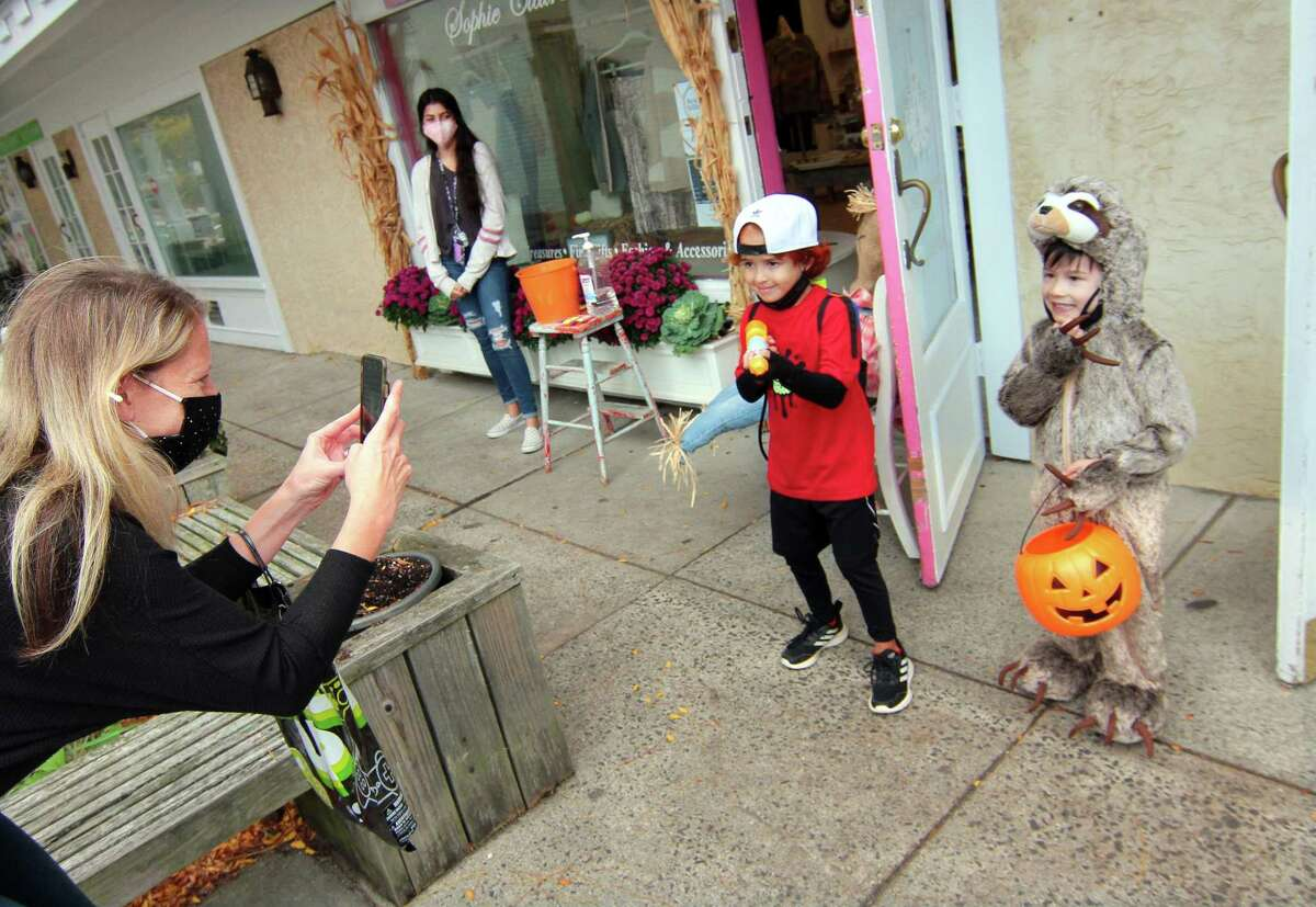 Jenn Field, of Orange, takes photos of her son Phoenix Field, 5, and his friend Miles Yuen, 5, at right, as they take part in a safe, socially distant way to enjoy the Halloween holiday in downtown Milford, Conn., on Saturday Oct. 24, 2020. Sponsored by Spinnaker Milford, participating shops put a scarecrow out front and offered treats to local kids.