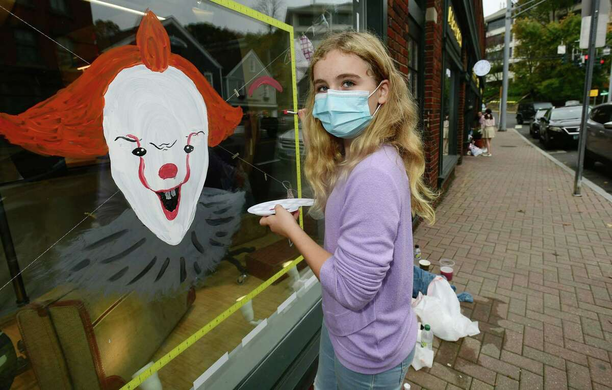 Sophie Jacques, 11, paints Pennywise the clown from the movie 'It' in the front window of Stephen Kempson London tailor in Westport as over 100 kids participate in the Westport-Weston Chamber of Commerce Halloween window painting competition on Saturday.