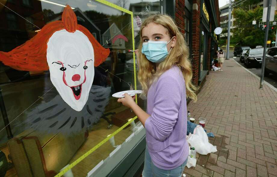 Sophie Jacques, 11, paints Pennywise the clown from the movie 'It' in the front window of Stephen Kempson London tailor in Westport as over 100 kids participate in the Westport-Weston Chamber of Commerce Halloween window painting competition on Saturday. Photo: Erik Trautmann / Hearst Connecticut Media / Norwalk Hour