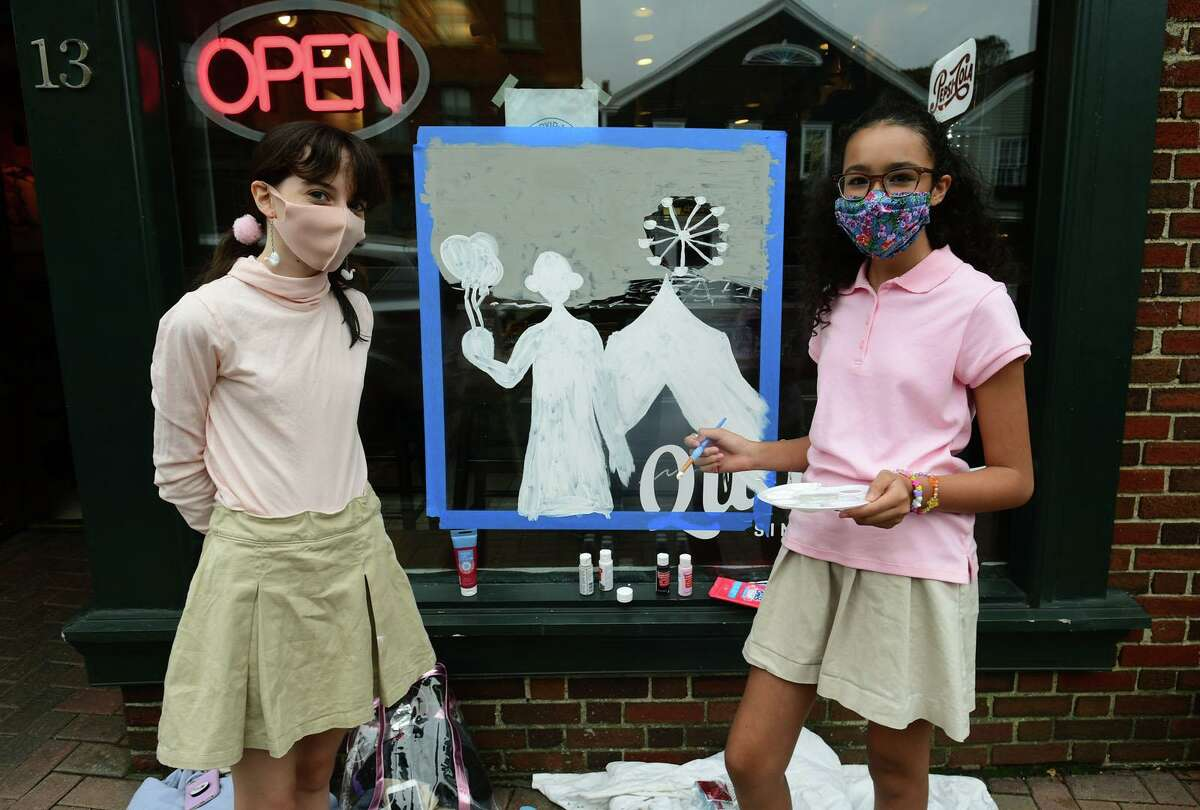Eliza Gurley and Stella Weinbrenner paint a clown in the front window of Winfield Deli as over 100 kids participate in the Westport-Weston Chamber of Commerce window painting competition Saturday, October 24, 2020, in Westport, Conn.