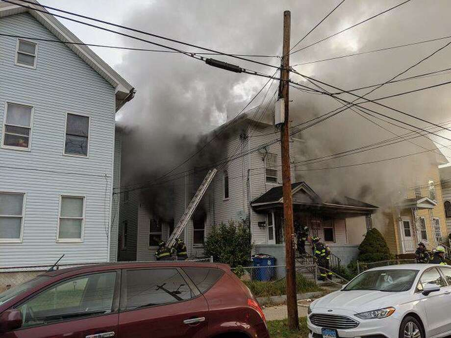 Smoke billows from a house on Spring Street Sunday, Oct. 25, in a photo by Lt. Christian Cordero tweeted by the New Haven Fire Department. Photo: Contributed Photo / New Haven Fire Department / New Haven Register Contributed
