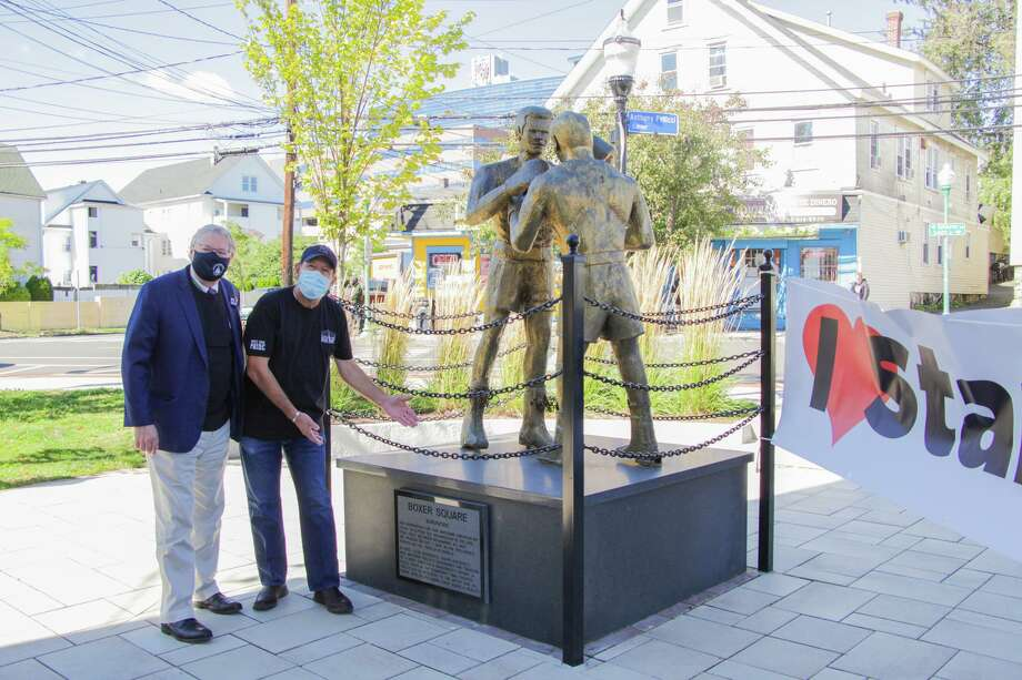 Jose Garay (right), owner of Jose's Barber Shop, poses with Mayor David Martin next to the statue of Muhammad Ali and Joe Frazier at Boxer Square, which was completely redesigned last year and is now up for a national award. Garay, whose business overlooks the square, cleans and cuts the grass at the square regularly, and said the new space is a point of pride. Photo: City Of Stamford