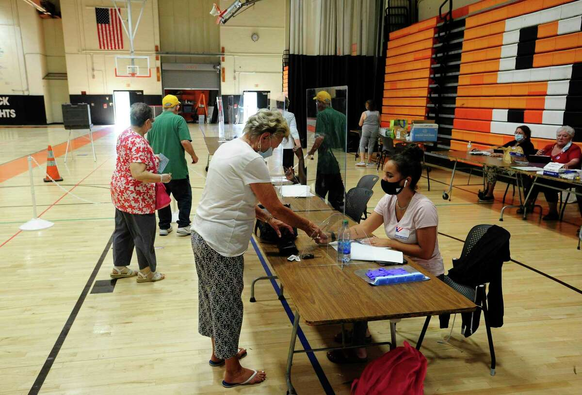 Voters check in at Stamford High School before casting their ballot in the presidential primary on August 11.
