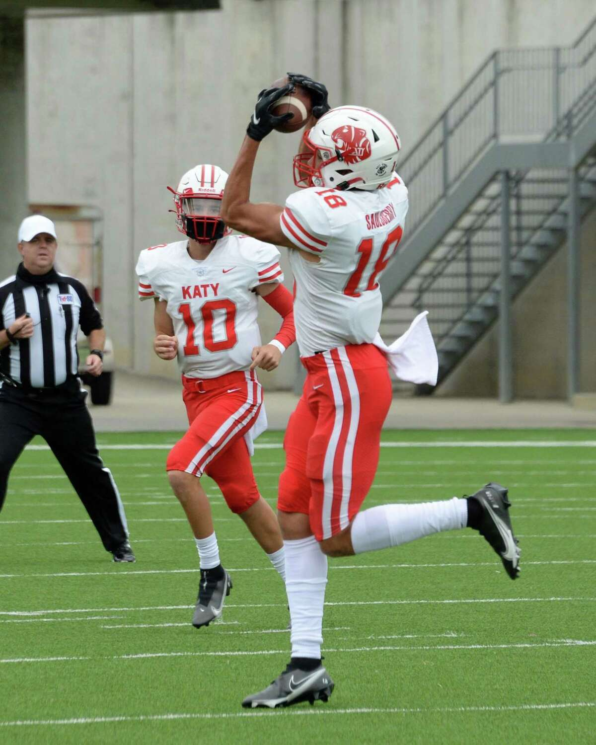 Taylor Saulsberry (18) of Katy catches a pass from Caleb Koger (10) and scores a touchdown during the second quarter of a 19-6A football game between the Cinco Ranch Cougars and the Katy Tigers on Saturday, October 24, 2020 at Legacy Stadium, Katy, TX.