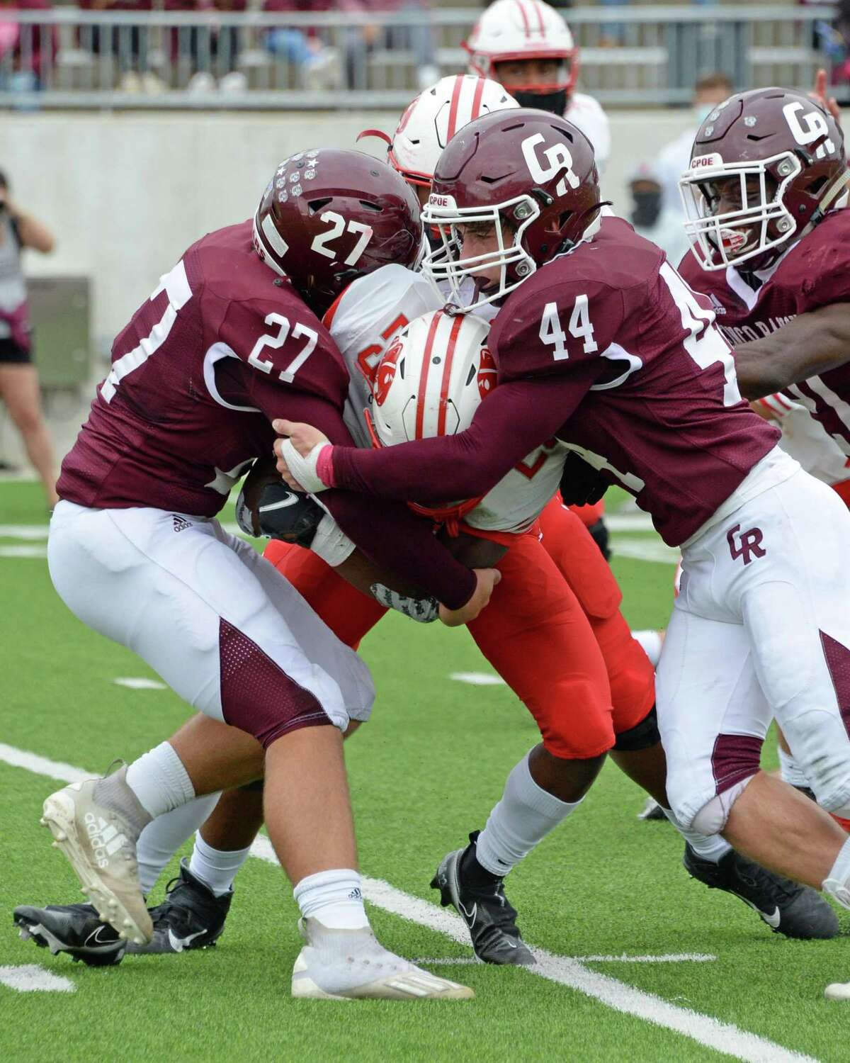 Nathan Rothwell (27) and Gracen Villafone (44) of Cinco Ranch tackle Seth Davis (23) of Katy during the second quarter of a 19-6A football game between the Cinco Ranch Cougars and the Katy Tigers on Saturday, October 24, 2020 at Legacy Stadium, Katy, TX.