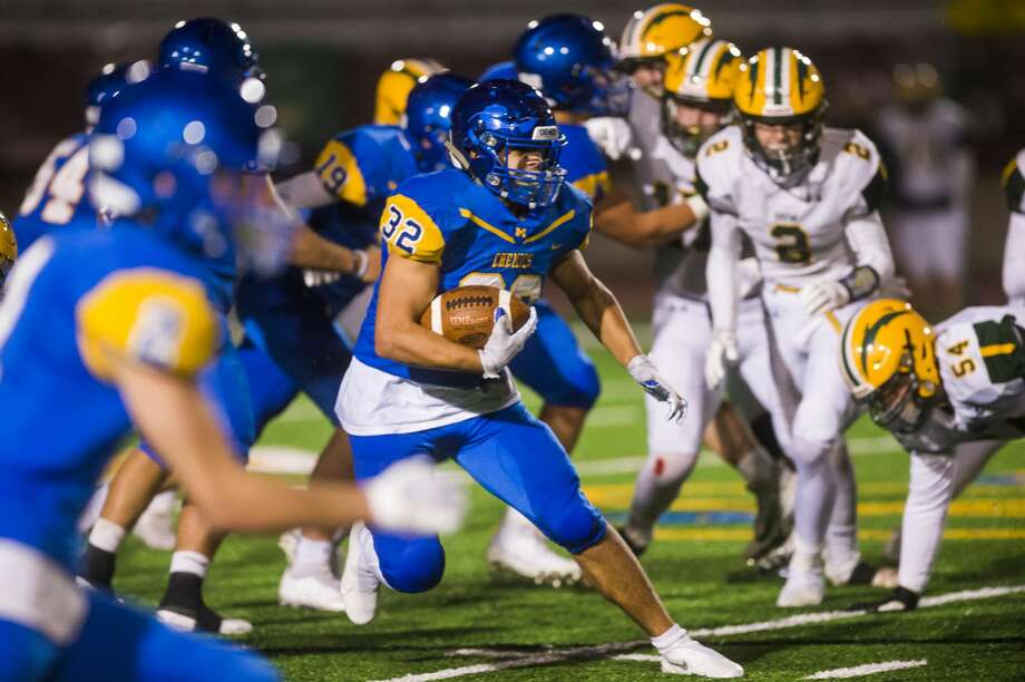 Midland High's Drew Johnson carries the ball during Friday's game against Dow High. Photo: Daily News File Photo